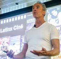 Frederick Luis Aldama speaks in front of a large screen displaying Latinx movie posters